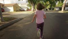 Happy 5 year old girl running on suburban street, chasing POV camera Slow motion Stock Footage