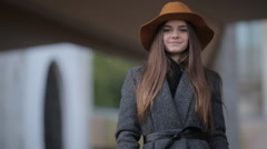 beautiful girl in a hat with a brim and coat stands near the University - stock footage