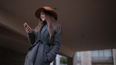 beautiful girl in a hat with a brim and a coat with a smartphone - stock footage