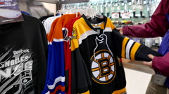 Woman picking one of Boston Bruins Premier Jersey cloth Stock Footage