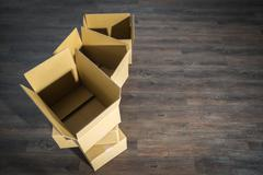 Pile of cardboard boxes on parquet  home relocation Stock Photos