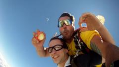 Skydivers eating apple in free fall Stock Footage