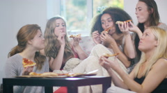 4K Happy young female friends having a sleepover & eating takeaway pizza - stock footage