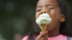 4K Portrait of African American brother & sister enjoying ice creams in the park - stock footage