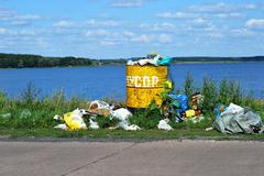 Overflowing barrel with rubbish and waste disposal on the waterfront Stock Photos