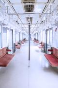 Empty seats and handrails inside commuter trains - stock photo