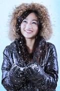 Joyful girl catching snowfall - stock photo
