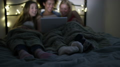 4K Young female friends having a sleepover, watching film or tv on computer - stock footage