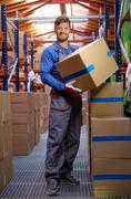 Porter carrying boxes in a warehouse Stock Photos