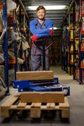 Loader using hand pallet truck in a warehouse Kuvituskuvat