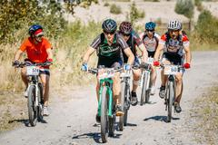 Group of mountain bike cyclists riding sandy track at sunny summ - stock photo