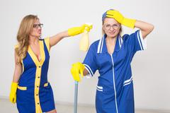 two different cleaners compete. poor staff - stock photo