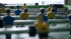 Table football game with yellow and blue players in slowmotion  on blurred Stock Footage