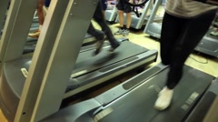 Several athletes running around on treadmills in the fitness club Stock Footage
