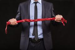 Man in business suit with chained hands. handcuffs for sex games Stock Photos