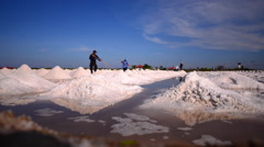 Time lapse of farmer piling up sea salt agriculture Stock Footage