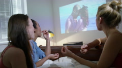 4K Young female friends having a sleepover, watching romantic film  - stock footage