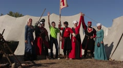 Happy smiley tourists with people in historical medieval costumes Stock Footage