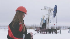 Female engineer and oil man working together in an oilfield, teamwork Stock Footage