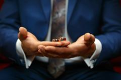 Gold wedding rings on a hand of the groom - stock photo