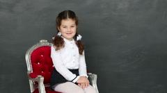 Little girl sitting in a chair near a school board Stock Footage