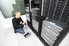 IT consultant calling for help in datacenter Stock Photos