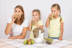 Mother and two daughters drink freshly juice from the pears and grapes - stock photo