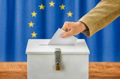 Man putting a ballot into a voting box - European Union - stock photo
