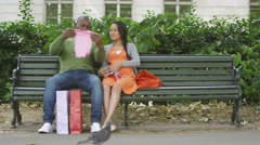 4K Happy couple expecting baby take baby clothes out of shopping bags to look at Stock Footage