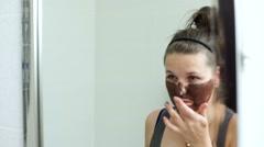 Young woman applying facial chocotate mask Stock Footage