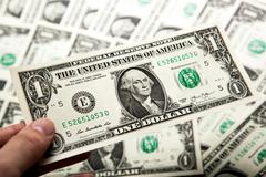 Stock Photo of hand holds a dollar bill