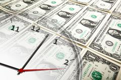 Clock on the background of banknotes dollars Stock Photos