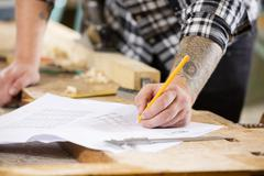 Carpenter plans project and writes at drawings in workshop Stock Photos