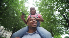 4K Happy African American father & daughter walking in urban park - stock footage
