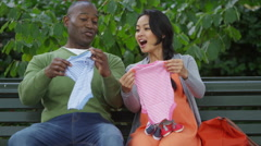 4K Happy couple expecting baby take baby clothes out of shopping bags to look at - stock footage