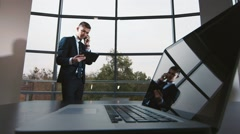 Young businessman working with the tablet: talking on a cell phone Stock Footage