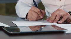 Man's hand writing text in documents Stock Footage