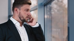 Tired businessman talking on a cell phone Stock Footage