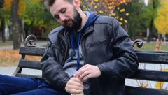 Tough guy drinking wine on a Park bench - stock footage