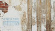 Stock Video Footage of Weathered and Cracked Wall with Vertical Visual Elements.