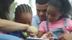 4K Happy African American family in the park looking at computer tablet.  - stock footage