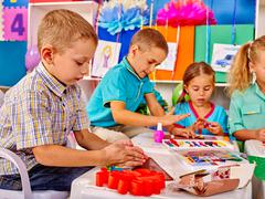Kids holding colored paper and glue on table in kindergarten - stock photo