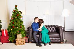 couple  kissing in christmas eve near tree with gifts - stock photo