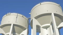 Concrete water towers in front of blue sky slow motion 4K 2160p UHD footage - Stock Footage
