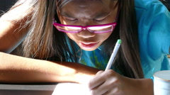 Asian Girl With Pink Glasses Draws Picture Stock Footage