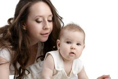 Nice dark-haired mother takes care of her child - stock photo