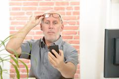 Mature man having trouble seeing phone screen because of vision problems - stock photo
