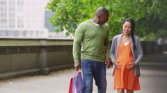 4K Happy couple expecting a baby walking with shopping bags in the city - stock footage