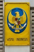 Label with the coat of arms of Indonesia on the gates of the embassy Stock Photos