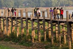 People crossing wooden bridge in Burma Stock Photos